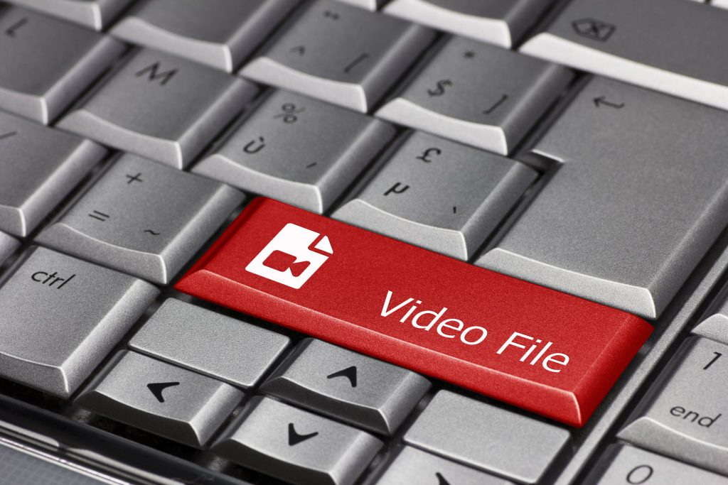 A large red video file button on a gray keyboard.